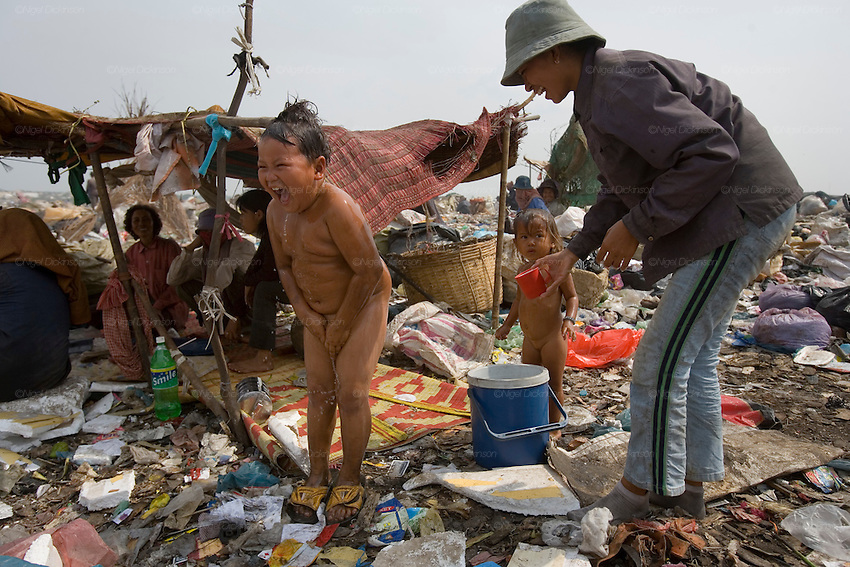 RUBBISH DUMP RECYCLING. South East Asia, Cambodia, Phnom Penh. Smokey Mountain, Steung Mean Chey, is Phnom Penh's municipal rubbish dump. Thousands work there, some 600 minors and 2000 adults, recycling the city's rubbish, dumped there by garbage trucks every day. The dump is notorious as many very young children work there. People eat and sleep overnight in the rubbish and fumes, under plastic tarpaulins or in the open air. They work 24 hours a day, like miners, with headlamps at night, collecting plastic, metals, wood, cloth & paper, which they sort and clean, weigh and sell, to be carried away for recycling. A day's work typically brings less than a dollar per person. One and a half to two dollars per day per family. The overpowering, acrid odour of grey smokey fumes blows across the dump, from which the place gets its name 'Smokey Mountain'. It can be smelt miles away. The shantytowns and squats, the recycling worker's homes butt onto or are inside the dump itself. There is no running water, sanitation and many are ill. Children often work with friends or relatives. Religious and ngo's help some children, but this is often resisted by families who need the extra income they generate.///A boy, sprayed by his mother from a bottle, takes a shower in the middle of Smokey Mountain
