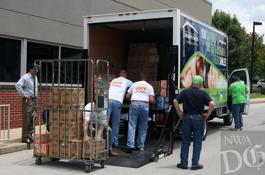 STAFF PHOTO SAMANTHA BAKER &bull; @NWASAMANTHA<br /> <br /> Employees from Mondelez International at the Northwest Arkansas Children's Shelter load donations into the new truck the Shelter received from the Walmart NW Arkansas Championship golf tournament Friday, June 20, 2014, at Mondelez International's office in Rogers. The larger-scale truck allows the NWA Children's Shelter to more easily pick up donations than their previous method.
