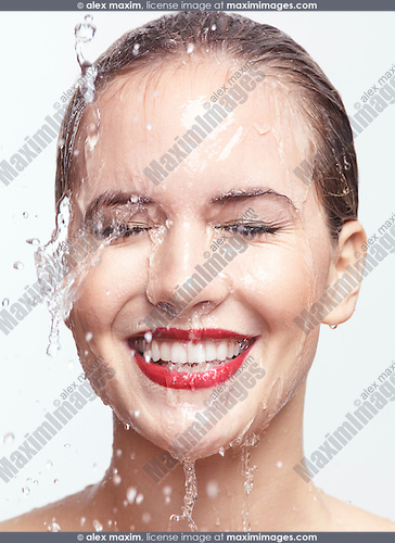 Artistic beauty portrait of a young smiling woman with water dripping over her face. Isolated on white background.
