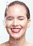 Artistic beauty portrait of a young smiling woman with water dripping over her face. Isolated on white background. Image © MaximImages, License at https://www.maximimages.com