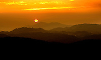 The setting sun turns the entire sky a brilliant orange as it sets behind North Carolina's Blue Ridge Mountains.