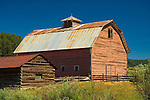 Faded red barn with log shed in the mountains of central Colorado
