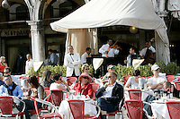 Turisti seduti nei bar all'aperto ascoltano la musica suonata dalle orchestre, in Piazza San Marco a Venezia.<br /> Tourist sit at outdoor cafes as orchestras play in St. Mark's Square, Venice.<br /> UPDATE IMAGES PRESS/Riccardo De Luca