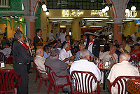 Mexican mariachi band serenading a table of elderly men in a restaurant on the main square in Veracruz city, Mexico