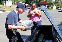 Crozet firefighter Tom Loach loads bottled water into the vehicle of Crozet resident Tina Howard. A truck load of bottled water was delivered overnight to the Crozet Fire department by the Virginia Emergency Management for residents in need. High winds from Friday night's storm downed numerous trees and caused massive power outages across the area.