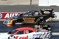 Feb. 17, 2013; Pomona, CA, USA; NHRA funny car driver Tony Pedregon (far lane) has a small fire going in the front wheel area alongside Gary Densham during the Winternationals at Auto Club Raceway at Pomona. Mandatory Credit: Mark J. Rebilas-