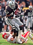 Oakland Raiders vs. Kansas City Chiefs at Oakland Alameda County Coliseum Sunday, November 5, 2000.  Raiders beat Chiefs  49-31.  Kansas City Chiefs defensive back Jerome Woods (21) attempts to hold on to Oakland Raiders running back Tyrone Wheatley (47).
