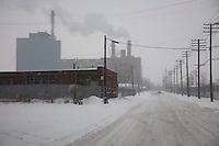Detroit: paesaggio urbano d'inverno. Una strada innevata. Vecchi palazzi e due comignoli fumanti su un grosso edificio.