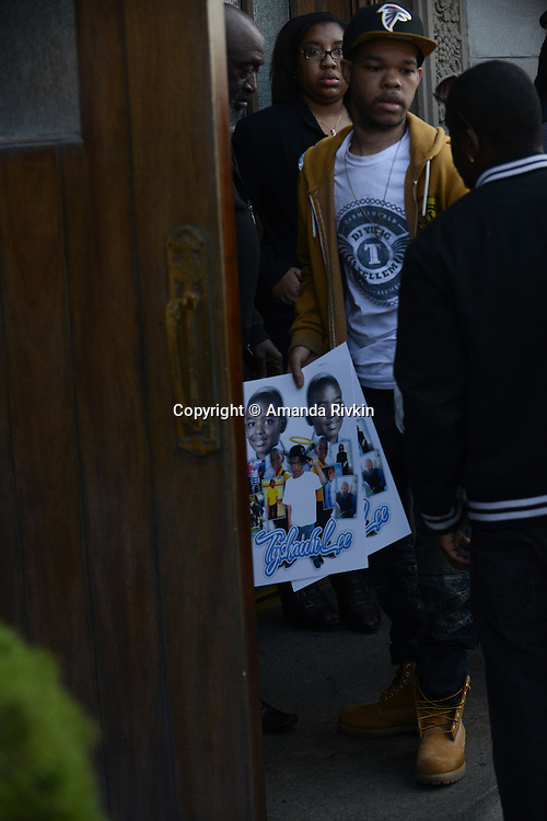 A mourner carries posters of Tyshawn Lee, 9, who was shot multiple times while playing basketball in an alley on November 2, 2015, to the funeral at St. Sabina's in Chicago, Illinois on November 10, 2015. Police allege the killing was a retaliatory gang hit which would mark a new turn in Chicago's gang wars.