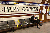 A man reads a  book on the platform at Hyde Park Corner underground station.
