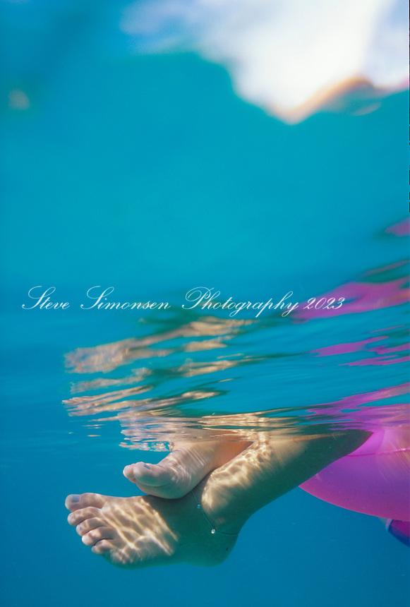 Feet of someone relaxing on an inner tube floating in the ocean<br /> U.S. Virgin islands