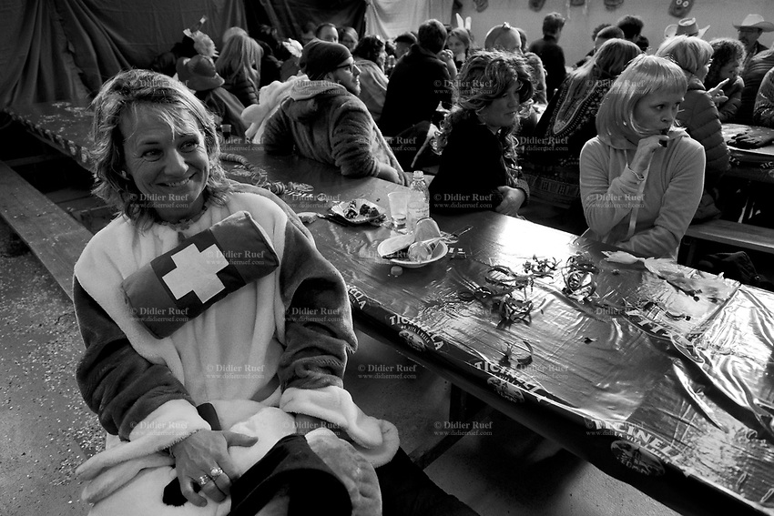 Switzerland. Canton Ticino. Carona. People are disguised for the carnival's celebrations. A laughing woman is dressed up as a St. Bernard dog with a swiss flag barrel on her chest. Serpentine streamers, food, plastic plates, aluminium cans and plastic bottle laid on the table. The St. Bernard or St Bernard is a breed of very large working dog from the western Alps in Switzerland, They were originally bred for rescue and famous for their iconic barrel.The breed has become famous through tales of alpine rescues, as well as for its enormous size. Carona is quarter of the city of Lugano and a former municipality in the district of Lugano. Carnival is a Western Christian festive season that occurs before the liturgical season of Lent. A serpentine streamer is a type of party accessory made out of long strips of paper, wound up in a roll. When thrown up in the air they create beautiful serpentines, and their motion through air is fun and aids in party cheerfulness. Serpentine streamers usually come in rolls that contain multiple strips. They have to be separated into smaller rolls before use. 4.02.2018 © 2018 Didier Ruef<br /> <br /> <br /> <br /> .
