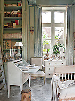 A formal sitting room decorated in turquoise tones and, unusually, a concrete floor. The room is furnished with antique pieces in the Gustavian style.