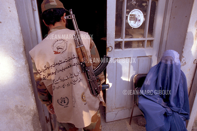 A woman  health worker wait for the vaccine distribution as an armed guard control the entrance of the pharmacy at the Herat General Hospital in the morning of the national immunization days in Herat, Afghanistan, on April 16, 2002.(photo by Jean-Marc Giboux)