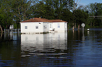 A bird passes by a home in the Red Star District of Cape Girardeau, MO, on Wednesday, May 4, 2011. Since the Birds Point levee was intentionally breached by the Army Corps of Engineers on Monday, May 2, 2011, the Mississippi River floodwater have receded at least two feet, according to resident Peggy Benaivdz.