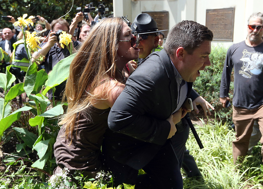 A woman tackles Jason Kessler after his press conference was disrupted by protestors Sun., August 13, 2017 outside City Hall in Charlottesville, Va. The previous day, a woman was killed and several others injured after the Unite the Right rally, organized by Jason Kessler. Photo/Andrew Shurtleff