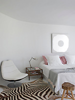 A dramatic zebra-skin rug in the otherwise contemporary whitewashed bedroom
