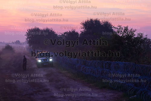 Officers in a police car search after illegal migrants crossing the border between Hungary and Serbia near Roszke (about 174 km South of capital city Budapest), Hungary on August 30, 2015. ATTILA VOLGYI