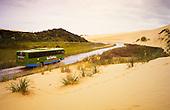 A tourist bus heads down Te Paki Stream to Ninety Mile Beach. Northland, New Zealand.