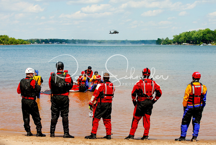 On-location photography of helicopter aquatic rescue team training on Lake Norman. Members of the North Carolina Helicopter and Aquatic Rescue Team (NCHART) refresh their skills during training exercises in May 2012 on Lake Norman. More than 60 National Guards troops, first responders and emergency management officials from across the state will spent four days practicing rescuing survivors in various lake conditions. NCHART combines the expertise of local rescue technicians with the training, maintenance and capabilities of the N.C. National Guard and the N.C. Highway Patrol Aviation units. The NCHART program became the first of its kind in the nation to implement a regimented training and response program that combines the best civilian rescuers with military aviation assets. HART teams were used extensively following hurricanes Frances and Ivan in 2004 to rescue an estimated 350 residents from fast moving water and areas isolated when landslides cut off roads and escape routes. Since then, the teams also have rescued numerous stranded or injured hikers from remote mountainous regions..Participating agencies: N.C. Emergency Management; N.C. National Guard; Lincoln County Emergency Management; Lincoln County Sheriffs Office; Fire Departments from Denver, East Lincoln, Sherrills Ford-Terrell, Mooresville, South Fork, Union, Asheville and Charlotte; Lincoln County EMS; Lincoln County Water Rescue Team; N.C. Wildlife; US Coast Guard Auxillary; Gaston EMS; Lincoln and Cleveland county Local Incident Management Teams; and North Carolina All-Hazards Incident Management Team.