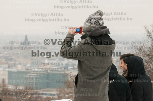 Tourists takes photo of the view of the city center from a hill top in Budapest, Hungary on January 19, 2013. ATTILA VOLGYI