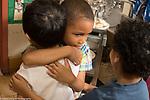 Education Preschool 3-4 year olds classroom scenes empathy boy giving sad boy a hug, another boy joining in