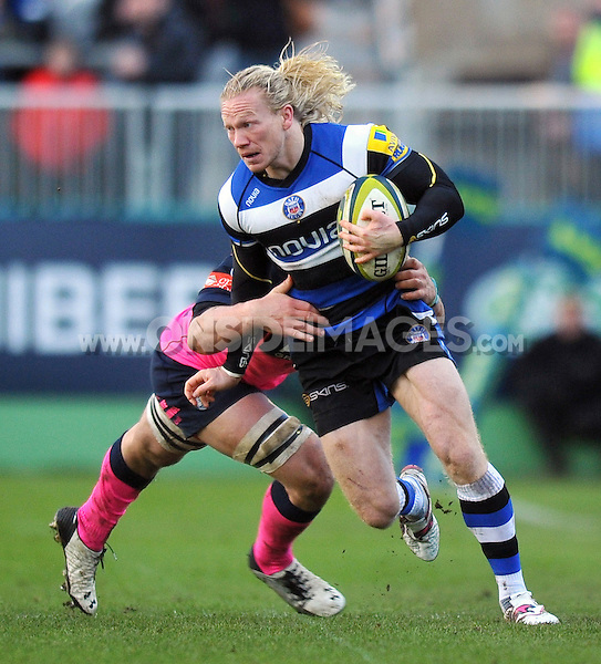 Tom Biggs is tackled in possession. LV= Cup match, between Bath Rugby and Cardiff Blues on January 25, 2014 at the Recreation Ground in Bath, England. Photo by: Patrick Khachfe / Onside Images