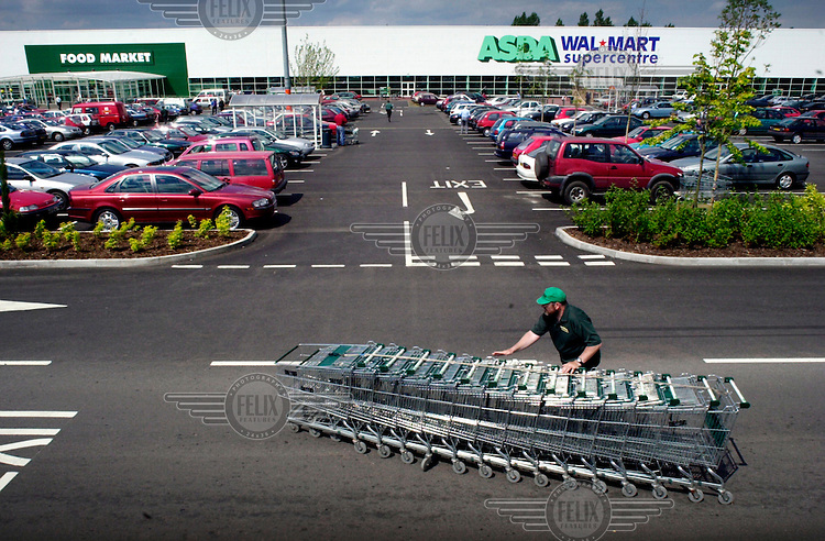 A car park attendant collects the shopping trolleys outside the Asda Walmart Supercentre supermarket at Cribbs Causeway in Bristol.