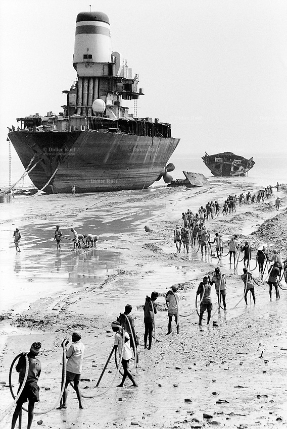 India. Province of Gujarat. Alang. Workers, all men, carry a wire to draw by winch a huge scrap's piece on the beach. Ships aground. Vessels stranded. Bottoms of ships at low tide on the shore. Alang is located in the Gulf of Khambhat on the Oman sea and is a ships breaking place. Alang, located in the Gulf of Khambhat, is a ships breaking place and is considered as the biggest scrapyard in the world. Ships recycling for its metals. Environmental issues. Hazardous waste. © 1992 Didier Ruef