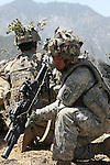 Spc. James Corona, 21, of San Antonio, Texas, a soldier with Company A, 2nd Battalion, 503rd Parachute Infantry Regiment, loads a M203 grenade round as his squad ambushes a group of Taliban fighters who have stumbled upon them during an operation in the Narang valley, in Kunar province, Afghanistan. The soldiers were protecting a team during a two-day mission that directed air and artillery strikes on Taliban positions in the valley below. May 17, 2008. DREW BROWN/STARS AND STRIPES