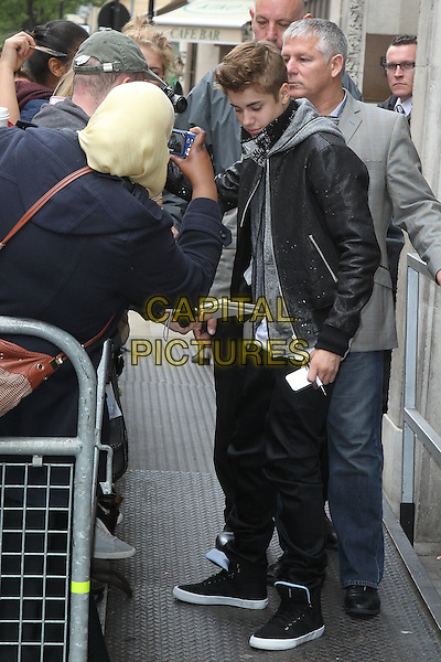 Justin Bieber at BBC Radio 1, London, England..June 6th, 2012.full length black jacket jeans denim grey gray hood fans signing autographs  leather .CAP/HIL.©John Hillcoat/Capital Pictures .