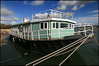 BNPS.co.uk (01202 558833)<br /> Pic: RiverSales&amp;Lettings/BNPS<br /> <br /> ****Please use full byline****<br /> <br /> A 100-year-old barge once used to ship cargo up and down the River Thames has been transformed into a plush four-bedroom house that is now on the market for &pound;450,000.<br /> <br /> The 90ft boat was salvaged from the banks of Thames in the 1970s and turned into a floating dormitory for schoolchildren at an outdoor activity centre.<br /> <br /> But it has since been given a complete makeover and now looks more like a cosy country cottage than a boat.<br /> <br /> The two-storey houseboat runs off mains electricity, has wifi access, electric heating, and hot water, and it also has a reserve water tank stored in its funnel.<br /> <br /> And buyers can count the picturesque River Hamble near Southampton, Hants, as their back garden.