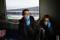 NEW YORK, NEW YORK - MARCH 03 : People wear face masks as they ride the air train inside the John F. Kennedy International Airport in New York on March 03, 2020. New York confirms second coronavirus case, as flights cancelations and Jewish schools close over virus fears.The first person to test positive for coronavirus in the state is a 39-year-old health-care worker who arrived from Iran with her husband, the second one is an attorney who lives in Westchester County, works in Manhattan, Gov. Andrew Cuomo said. (Photo by Eduardo Munoz / VIEWpress via Getty Images)