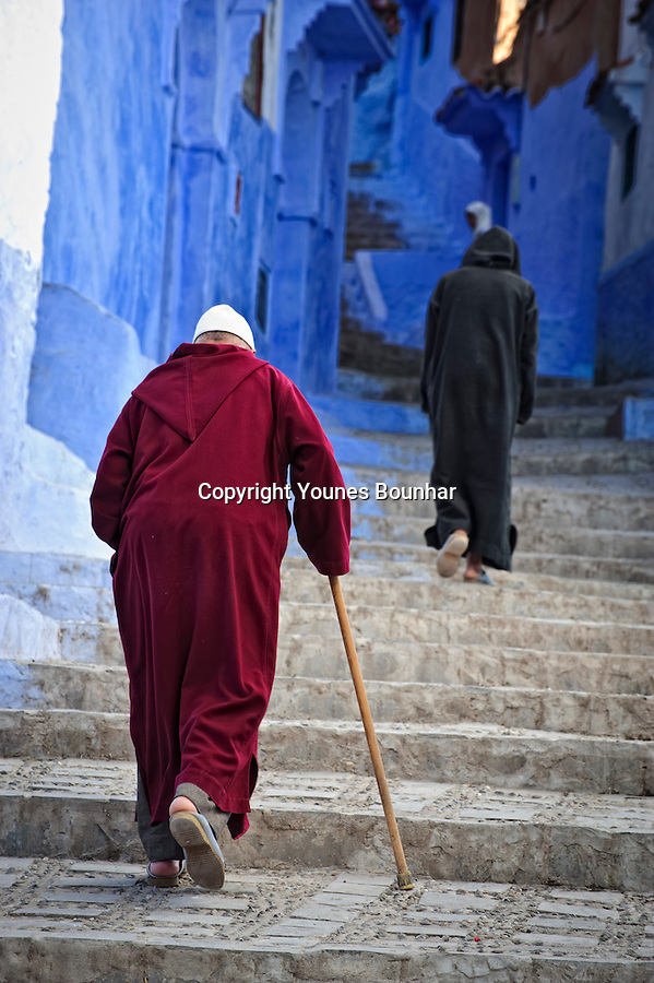 Two older men make their way up a steep stairway in the mesmerizing blue streets of Chefchaouen (at the foot of the Rif mountains of Morocco)