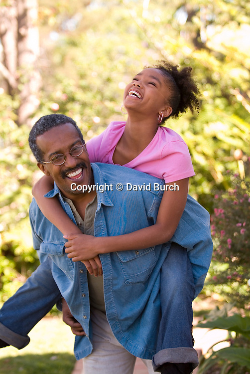 Grandfather carrying granddaughter, laughing