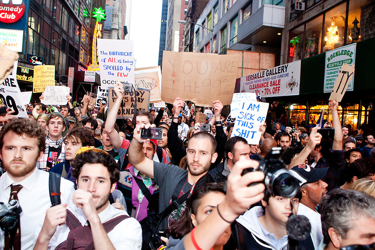 """Upon arriving at 46th Street and Broadway protesters with """"Occupy Wall Street"""" are met by police barricades that prevent them from totally """"taking"""" Times Square on October 15, 2011 in New York City.  While crowd estimates numbered in the tens of thousands, police tactics (including nets, motor scooters, barricades, arrests, and intimidation by riders on horseback) prevented the crowd, which had been split up, from joining together as one in the middle of Times Square."""