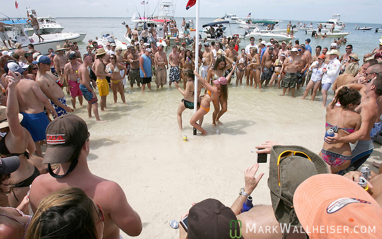 Memorial Day weekend celebrants watch three girls pole dancing on a Confederate flag adorned pole that was erected in the surf at Dog Islance for the weekend long White Trash Bash at Dog Island off the coast of Carrabelle Sunday May 27, 2007. (Photo by Mark Wallheiser/TallahasseeStock.com)  (Mark Wallheiser/TallahasseeStock.com)