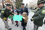 Sheriff Ken Furlong and Gov. Brian Sandoval give commemorative signs to the children of Carson City Sheriff's Dep. Carl Howell during a ceremony at the Nevada Law Enforcement Officers Memorial in Carson City, Nev., on Tuesday, Dec. 8, 2015. Officials unveiled a freeway sign dedicating I-580 in honor of Dep. Howell, who was killed in the line of duty Aug. 15, 2015. <br /> Photo by Cathleen Allison/Nevada Photo Source