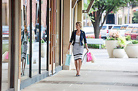 Beautiful woman with many shopping bags window shops at a popular outdoor shopping mall in Austin, Texas