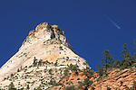 Jet airplane contrail in blue sky over mountain peak, Zion National Park, Utah