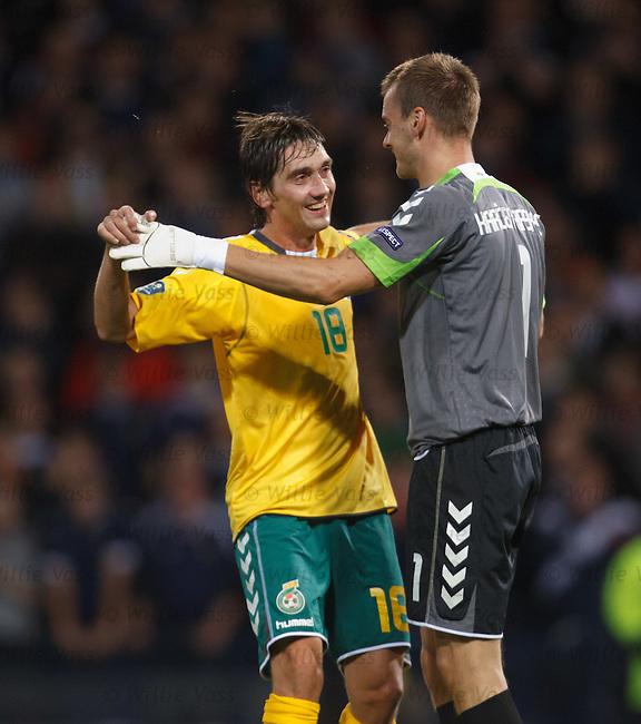 Deividas Cesnauskas celebrates with Lithuania keeper Zydrunas Karcemarskas as he saves the Scotland captain's penalty kick