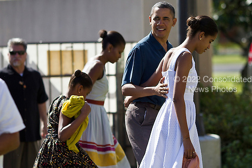 United States President Barack Obama, First Lady Michelle Obama and daughters Malia and Sasha Obama enter the Marine Corps Base Hawaii Chapel to attend Christmas services in Kaneohe, Hawaii, Sunday, December 25, 2011.  Obama is spending the Christmas holiday in his native Hawaii with his family. .Credit: Kent Nishimura / Pool via CNP