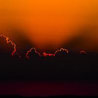 Sun setting behind clouds.