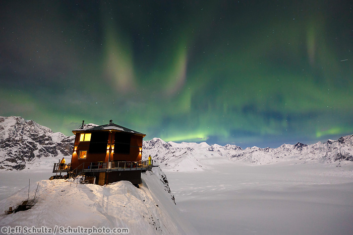 The Sheldon Chalet sits on a ridge under the Aurora Borealis (aka Northern Lights) in the Ruth Glacier and Amphitheater in the Alaska Range.  Winter <br /> <br /> Photo by Jeff Schultz/SchultzPhoto.com  (C) 2017  ALL RIGHTS RESERVED