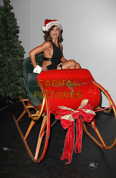 """KARINA SMIRNOFF.Karina Smirnoff celebrates her engagement and hosts """"The Ultimate Girls Night Out"""" at Chippendales at the Rio All Suite Hotel and Casino, Las Vegas, Nevada, USA, .10th December 2010..half length black dress hat santa red christmas xmas sitting in sleigh .CAP/ADM/MJT.© MJT/AdMedia/Capital Pictures."""