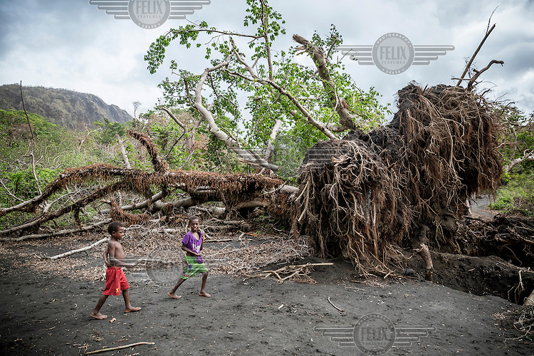 Children from Sulphur Bay village walk past trees uprooted by Cyclone Pam. <br /> Cyclone Pam, a tropical storm that hit the Pacific island nation of Vanuatu on 13 March 2015, is considered one of the worst natural disasters to affect the country. Over 15 people died in the storm and winds up to 165 mph (270 km/h) caused widespread damage to houses and infrastructure.