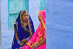 Rajasthani mother and daughter in traditional clothes sitting in front of house in Blue City (old town); the blue houses were originally for Brahmins but non-Brahmins soon joined in, as the colour was said to deflect the heat and keep mosquitoes away, Jodphur, Rajasthan, India --- Model Released