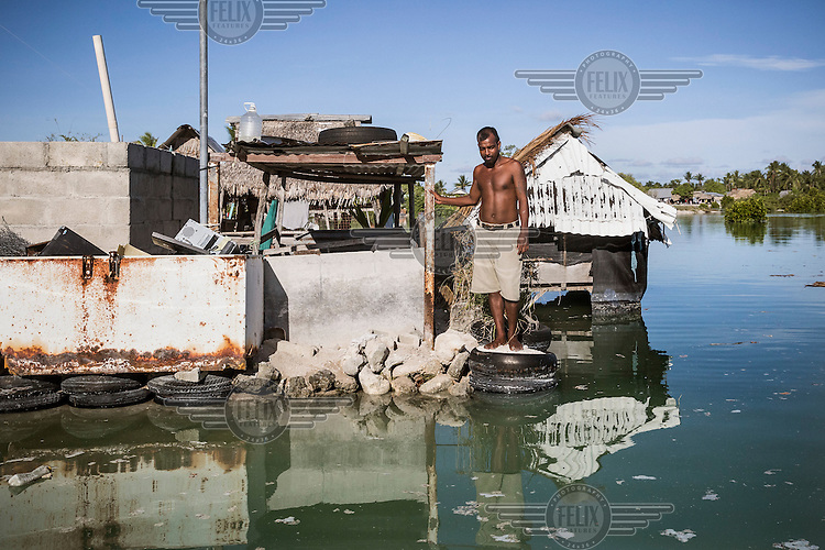 Aree Aupeia, 32, standing on the sea front near a house that gets regularly flooded during high tide events. The village is regularly flooded during high tides despite residents attempts to build sea walls or take care of those that were built by the local government, but frequent big waves continue to damage them, putting resident's houses, and gardens under the constant threat.
