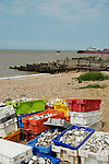 Whitstable beach with coloured crates containing oyster shells in the foreground and a container ship in the distance
