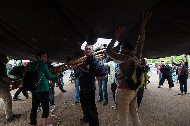 Fluechtlinge und Unterstuetzer bauen ein Informationszelt auf dem Oranienplatz auf.<br /> Am Mittwoch den 23. April 2014 bauten Fluechtlinge und Unterstuetzer im vierten Anlauf endlich ihr zugesagtes Informationszelt auf dem Oranienplatz in Berlin-Kreuzberg auf. Sie hatten dafuer eine Sondernutzungsgenehmigung durch den Bezirk sowie ein Schreiben der Senatorin fuer Soziales und Integration, Dilek Kolat. Fuer den Aufbau war extra der stellv. Bezirksbuergermeister und zustaendige Stadtrat fuer Wirtschaft, Ordnung, Schule und Sport Dr. Peter Beckers gekommen und erteilte auf dem Platz nochmals die Sondernutzungsgenehmigung und wies die Polizei an, den Zeltaufbau zu gewaehren.<br /> Die Polizei hatte in den vorangegangenen Tagen mehrfach den Aufbau verhindert. Mal war der Einsatzleiter der Meinung, die Genehmigung und das Schreiben der Senatorin haetten keine Bedeutung fuer den Aufbau, ein anderes Mal waren dem Einsatzleiter Abmessungen des Zeltes nicht recht. Am Dienstagabend noch eklaerte der zustaendige Einsatzleiter, die telefonische Anweisung des zustaendigen Stadtrates sei nicht rechtens, da er ja nicht wisse, wer am Telefon sei. In Berliner Medien wurde das Verhalten der Polizei zuletzt als &quot;Zelt-Posse&quot; bezeichnet.<br /> 23.4.2014, Berlin<br /> Copyright: Christian-Ditsch.de<br /> [Inhaltsveraendernde Manipulation des Fotos nur nach ausdruecklicher Genehmigung des Fotografen. Vereinbarungen ueber Abtretung von Persoenlichkeitsrechten/Model Release der abgebildeten Person/Personen liegen nicht vor. NO MODEL RELEASE! Don't publish without copyright Christian-Ditsch.de, Veroeffentlichung nur mit Fotografennennung, sowie gegen Honorar, MwSt. und Beleg. Konto:, I N G - D i B a, IBAN DE58500105175400192269, BIC INGDDEFFXXX, Kontakt: post@christian-ditsch.de<br /> Urhebervermerk wird gemaess Paragraph 13 UHG verlangt.]